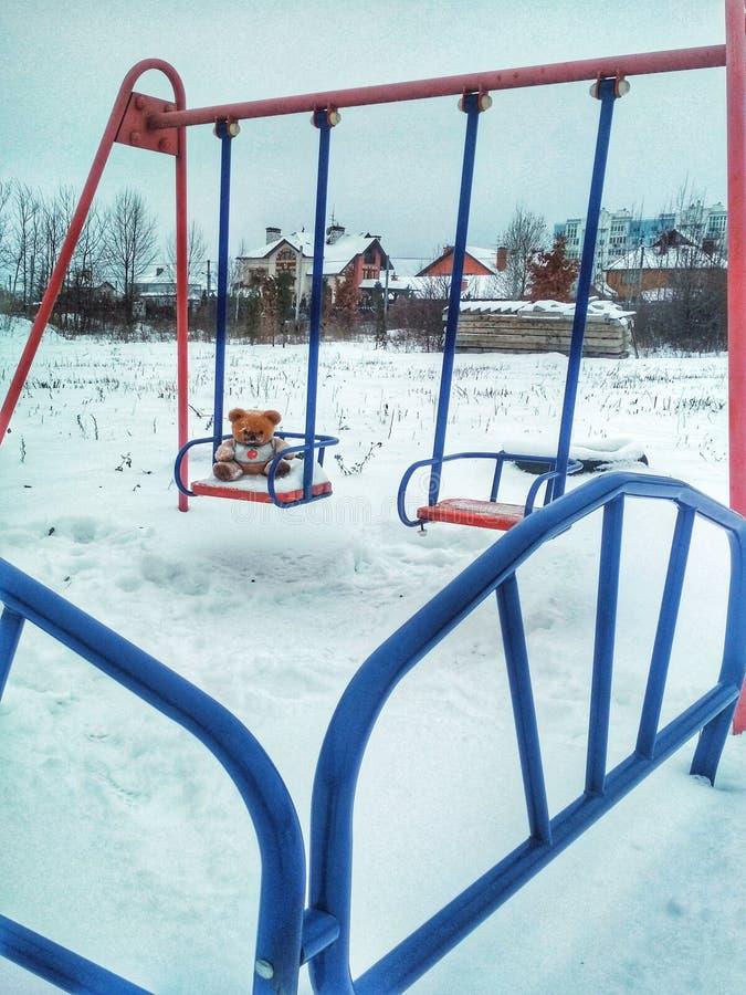 Urso de peluche macio do brinquedo no balanço das crianças no inverno fotos de stock