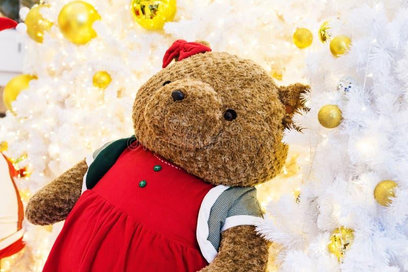 Urso de peluche marrom grande na árvore de Natal foto de stock