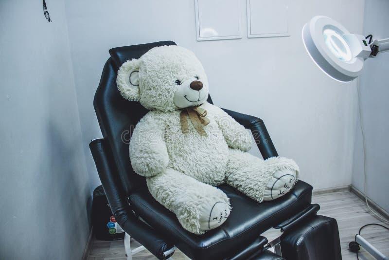 Urso de peluche na cadeira cosm?tica, lente de aumento da l?mpada para o esteticista, local de trabalho do esteticista, beauticia fotografia de stock
