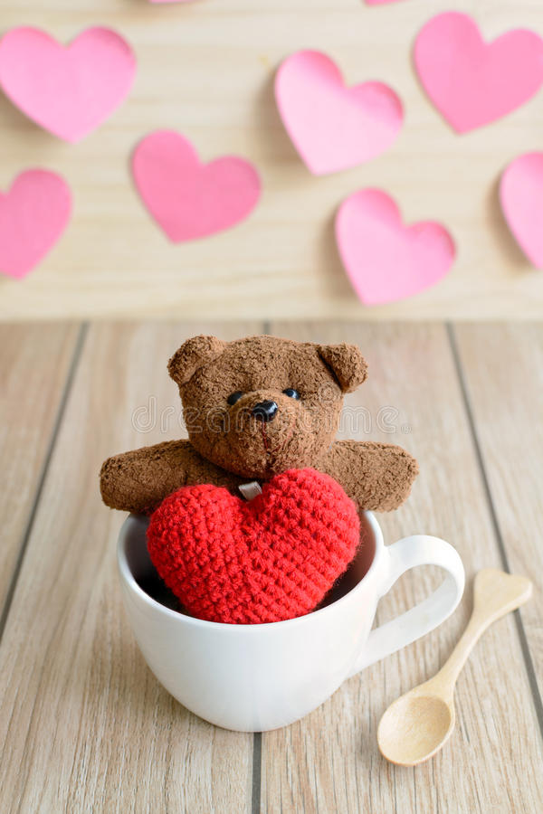 Urso de peluche na xícara de café com forma vermelha do coração na tabela de madeira imagem de stock
