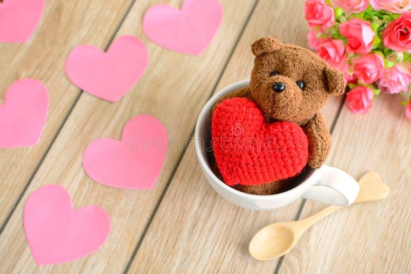 Urso de peluche na xícara de café com forma vermelha do coração na tabela de madeira fotos de stock royalty free