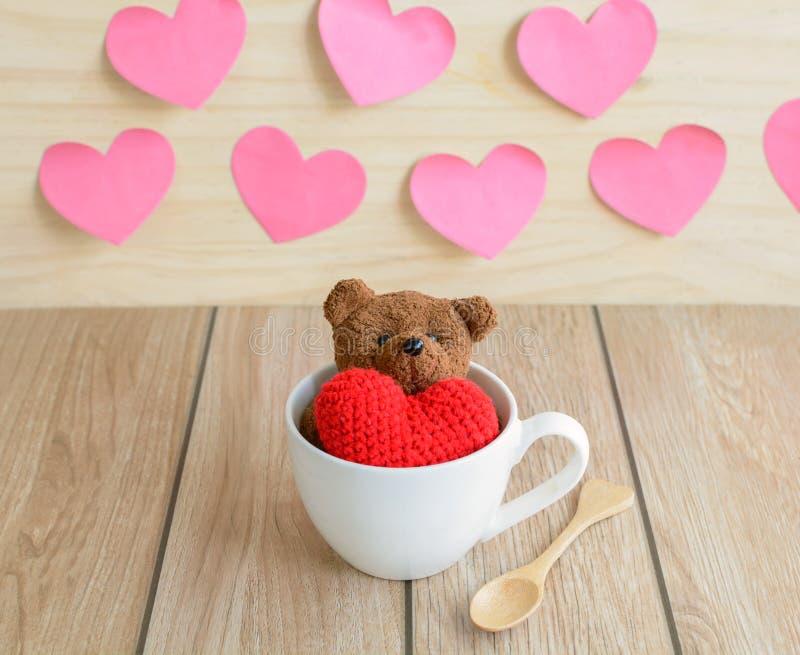 Urso de peluche na xícara de café com forma vermelha do coração na tabela de madeira imagens de stock