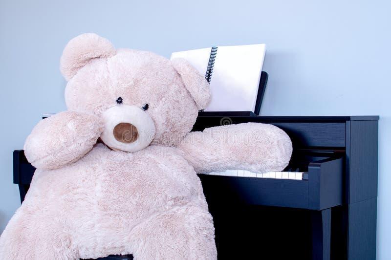 Urso de peluche no piano que faz a música imagens de stock royalty free