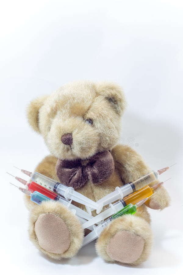 Urso de peluche que leva as seringas médicas plásticas que contêm líquidos coloridos imagens de stock