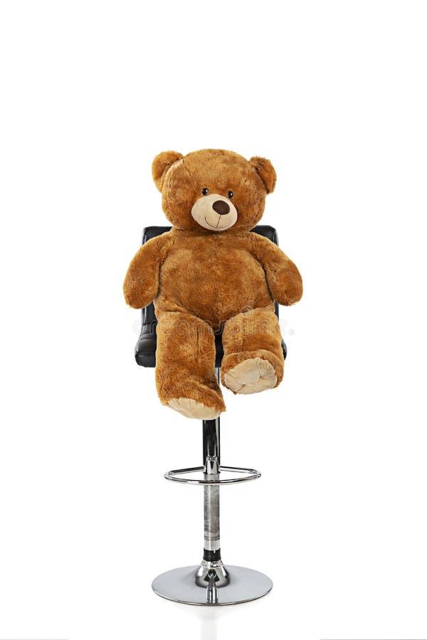 Urso de peluche que senta-se em um tamborete com um fundo branco fotografia de stock