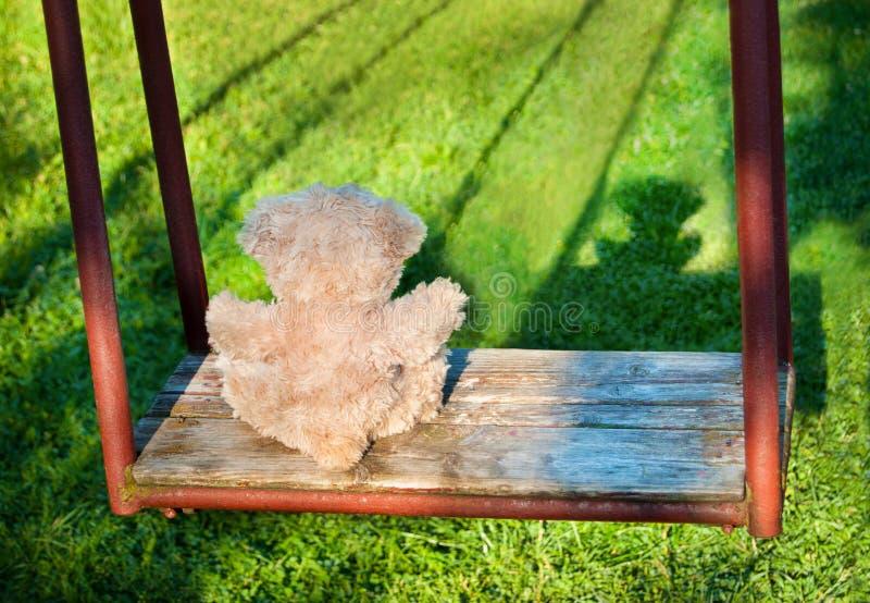 Urso de peluche que senta-se no balanço Conceito da solidão imagens de stock