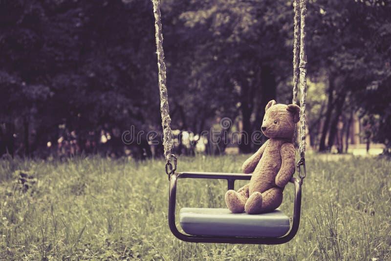 Urso de peluche velho do brinquedo que senta-se no balanço no parque imagens de stock