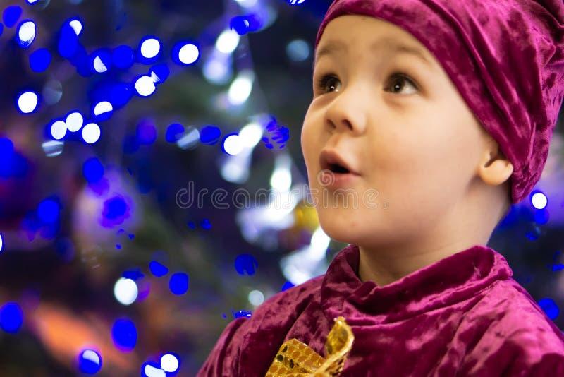 Urso do doce de fruta Menino emocional três anos velho em um traje roxo do urso no fundo de uma árvore do ano novo e de umas lant fotos de stock