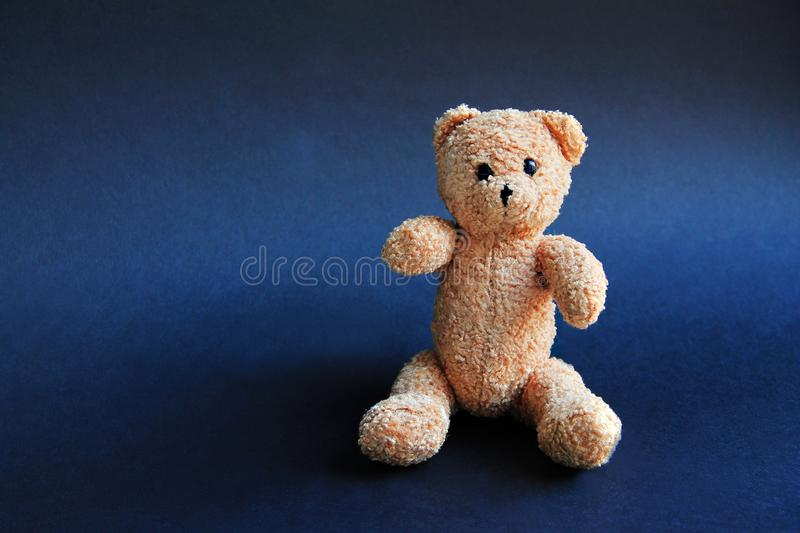 Urso macio do brinquedo de Brown no fundo preto fotos de stock royalty free