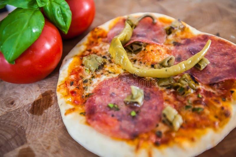 Ursprüngliches italienisches Pizza alla diavolo auf braunem hölzernem Hintergrund Pizza mit Peperoni und Salamiabschluß oben lizenzfreie stockfotos