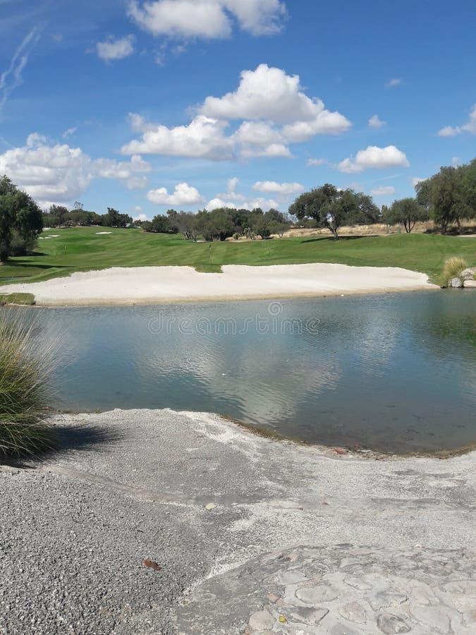 Ursprüngliche Golfplatz-Landschaftsszene mit weißem Sand, flaumige Wolken, See-Reflexion stockfotografie