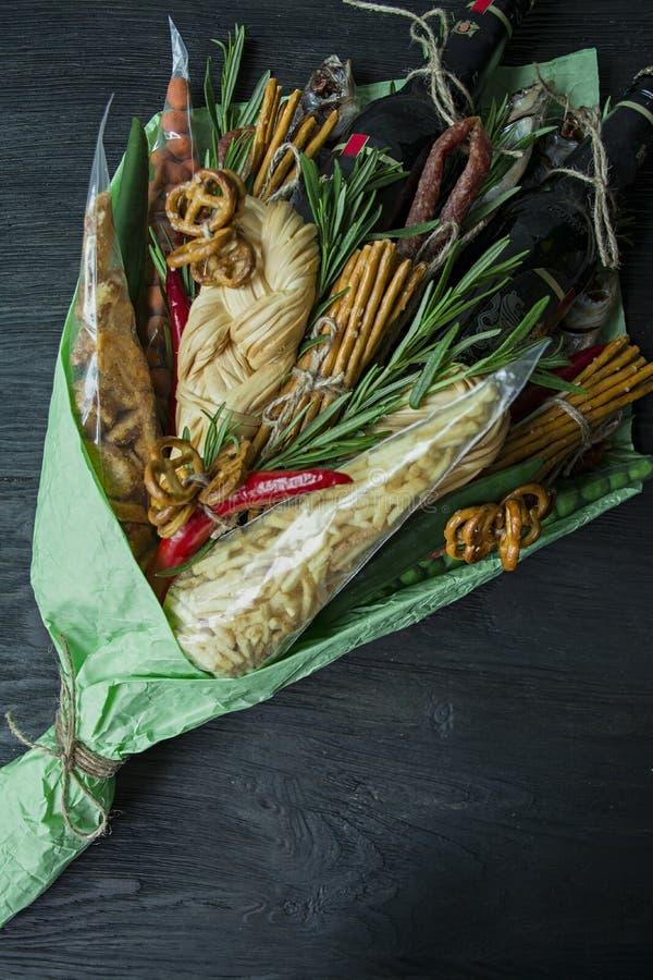 Ursprüngliches essbares Geschenk in Form eines Blumenstraußes, der aus Bier, Würsten, Käse, Bierimbisse besteht Mädchen hält essb stockbild