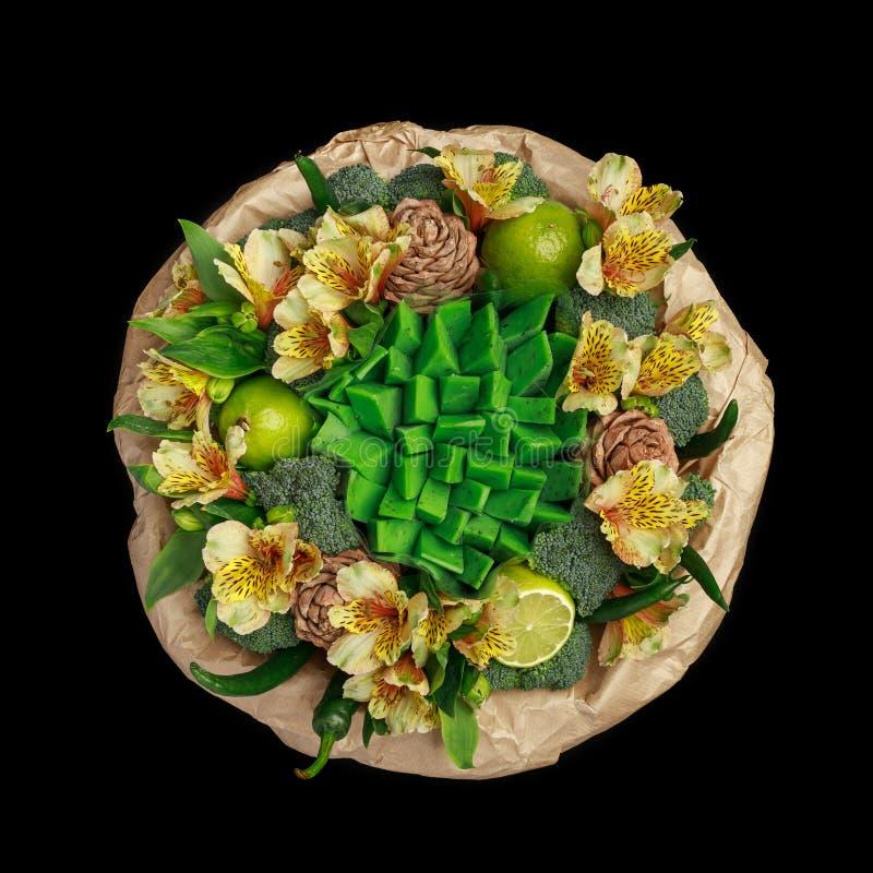 Ursprüngliches Geschenk in Form eines Blumenstraußes von Blumen, Gemüse und grüner Käse, stehend in einem Glasvase lokalisiert au stockbild