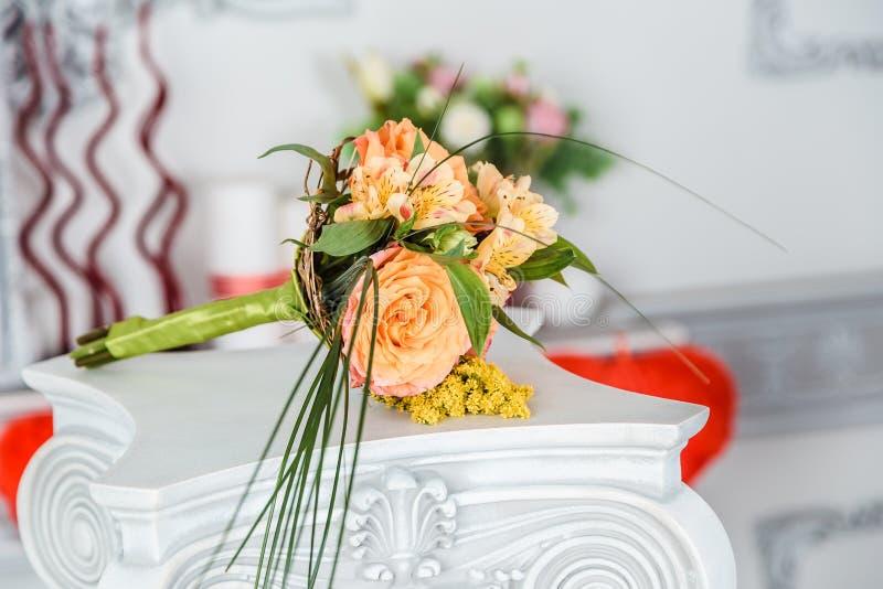 Urspr?nglicher kleiner Brautblumenstrau? von gro?en orange Rosen und von Mimosen stockfotografie