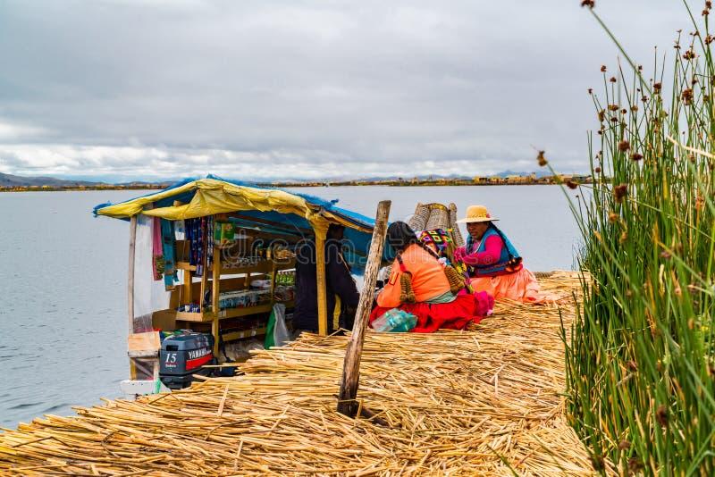 Uru kobieta jest ubranym tradycyjnych płótna kupuje karmowe i konieczne rzeczy od łodzi wprowadzać na rynek przy Uros Spławową wy zdjęcie stock