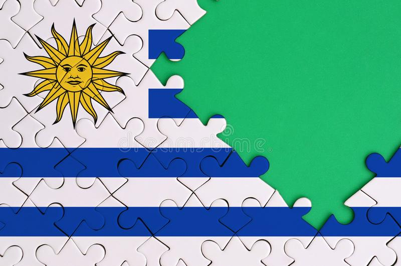 Uruguay flag is depicted on a completed jigsaw puzzle with free green copy space on the right side stock illustration