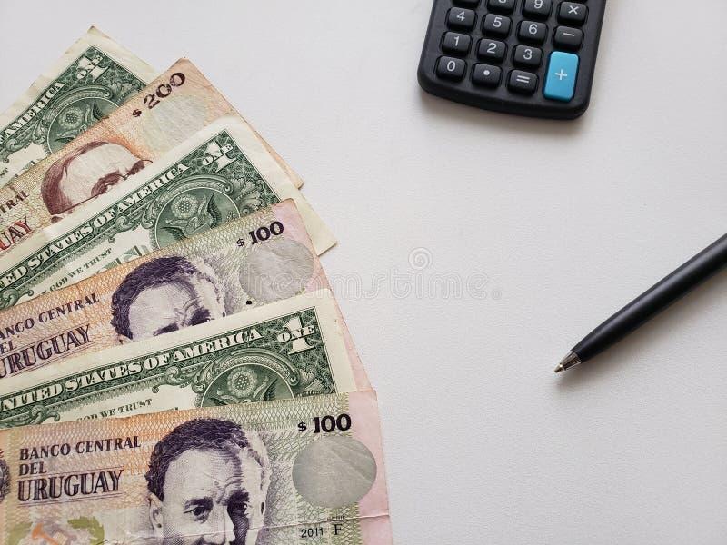 uruguayan bankbiljetten, Amerikaanse dollarrekeningen, calculator en zwarte pen op witte achtergrond royalty-vrije stock afbeeldingen