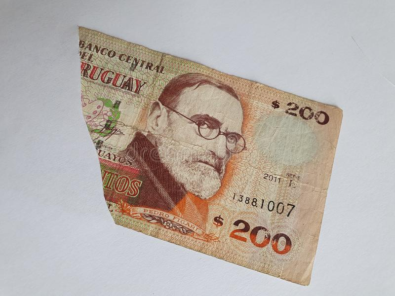 Uruguayan banknote of 200 pesos on the broken sheet of paper. Commerce, exchange, trade, trading, value, buy, sell, profit, price, rate, cash, currency, paper royalty free stock photos