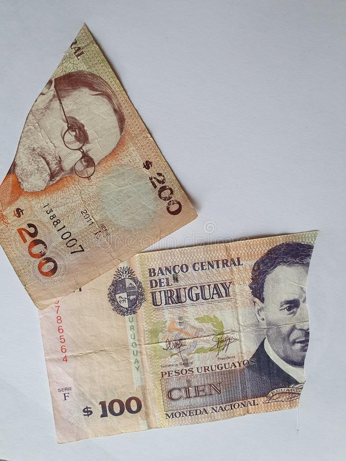 Uruguayan banknotes of different denominations on the broken sheet of paper. Commerce, exchange, trade, trading, value, buy, sell, profit, price, rate, cash royalty free stock photo