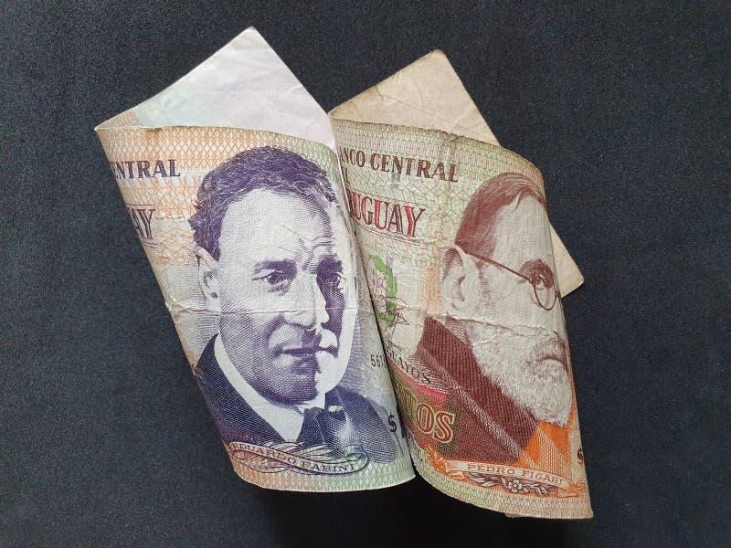 uruguayan sedlar av olika valörer och svart bakgrund arkivbild