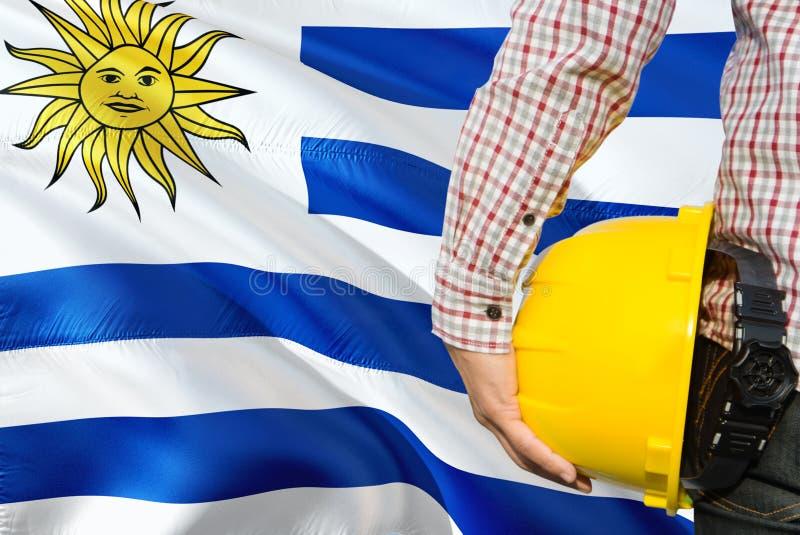 Urugwajski inżynier trzyma żółtego zbawczego hełm z machać Urugwaj chorągwianego tło Budowy i budynku poj?cie fotografia stock