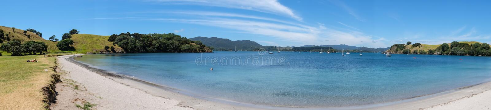 Urupukapuka Island, Bay of Islands, New Zealand, NZ - February 1. 2017: Tourists on an uncrowded beach in summer, with boats anchored in the bay royalty free stock image