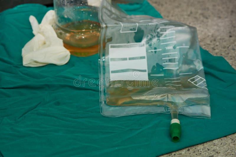 Uryna w plastikowej butelce i torbie , rozporządzalna rękawiczka na zielonym płótnie zdjęcia stock