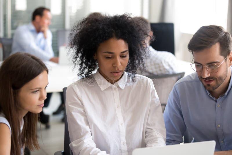 Urzędnicy z amerykanin afrykańskiego pochodzenia żeńskim liderem używa laptop obraz stock