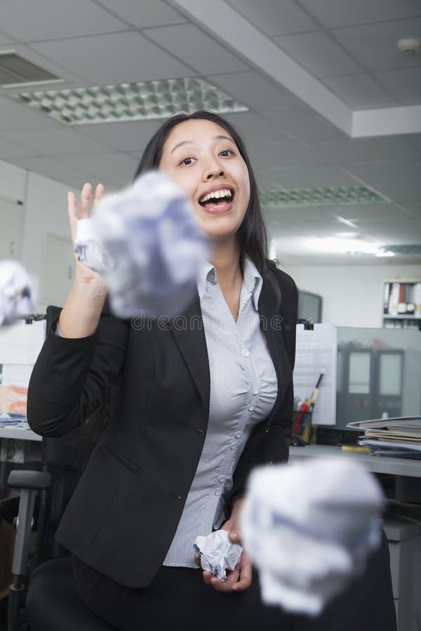 Urzędniczego pracownika miotania papier w biurze, mieć zabawę zdjęcia royalty free