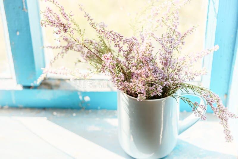 A urze floresce em um copo em uma janela de madeira velha em uma casa da quinta Estilo retro do vintage fotografia de stock