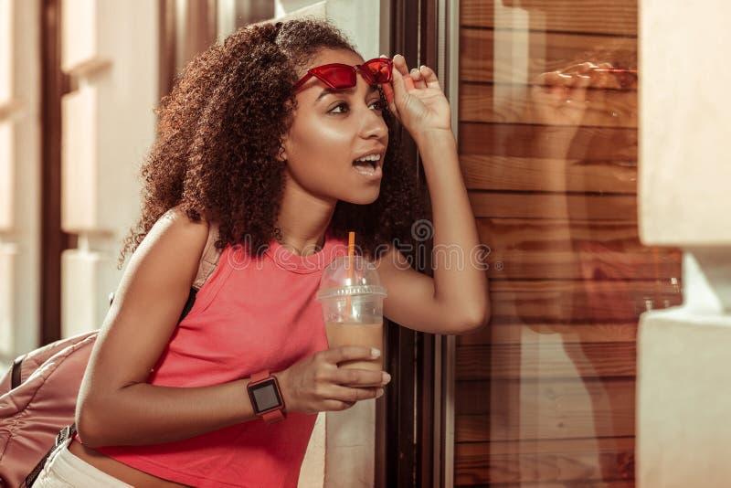 Urzekająca powabna amerykanina dorosłego kobieta patrzeje zaskakująco przy okno zdjęcie royalty free