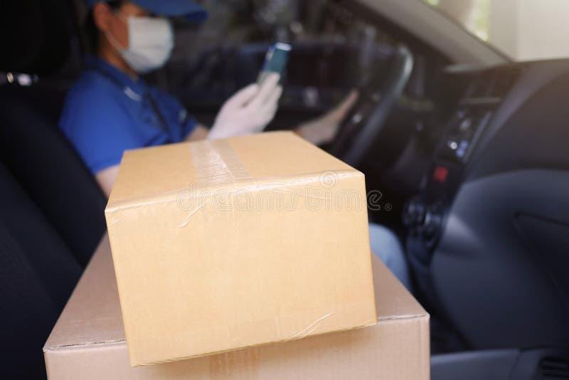 Usługi kurierskie w czasie pandemii COVID-19 Coronavirus, kartonowe pudełka na miejscu dostawczym z kurierzem w zdjęcia royalty free
