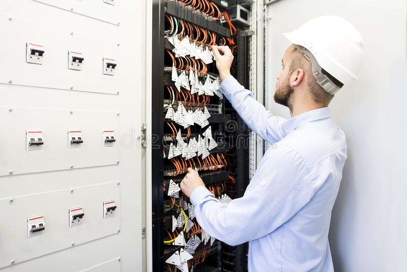 Usługowy inżynier w dane centrum Pracownik w hełmie blisko zmian okulistyczni kable zdjęcia stock