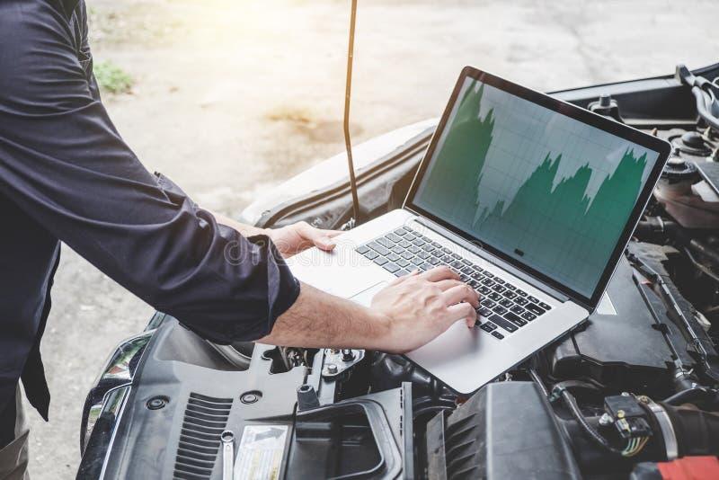 Usługuje samochodowego silnika maszynowego pojęcie, samochodu mechanika repairman sprawdza samochodowego silnika z używać kompute obraz stock