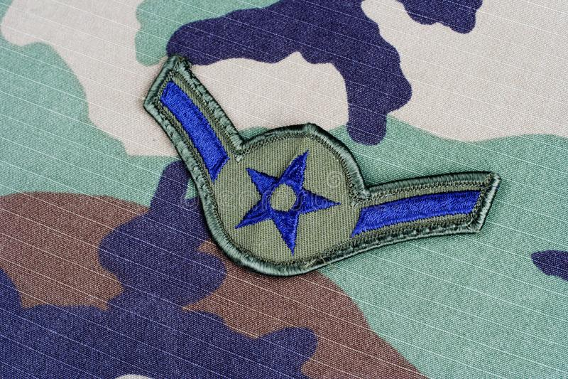 US AIR FORCE Airman rank patch on woodland camouflage uniform. Background royalty free stock image