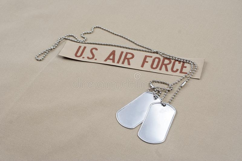 US AIR FORCE branch tape with dog tags on desert camouflage uniform. Background stock photo