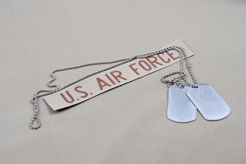 US AIR FORCE branch tape with dog tags on desert camouflage uniform. Background royalty free stock photography
