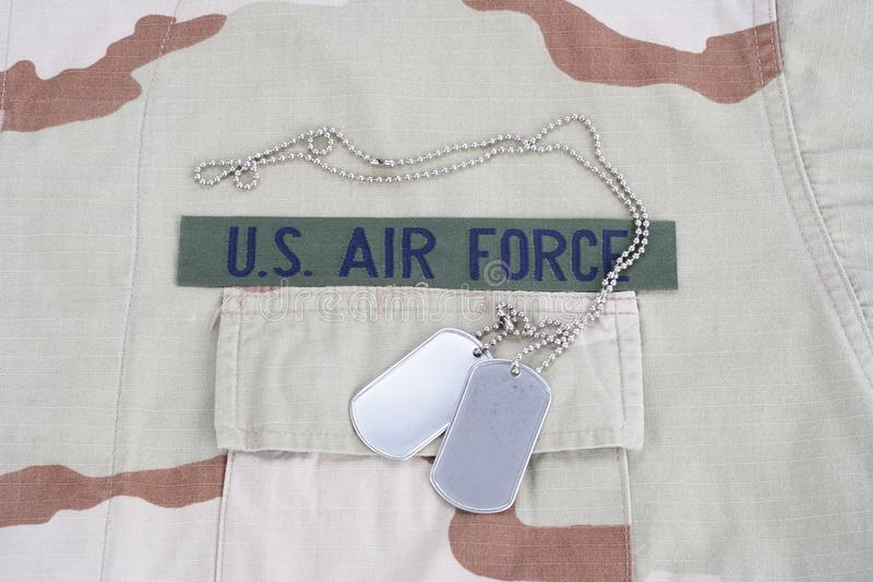 US AIR FORCE branch tape with dog tags on desert camouflage uniform. Background royalty free stock photo