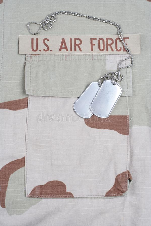 US AIR FORCE branch tape with dog tags on desert camouflage uniform. Background royalty free stock photos