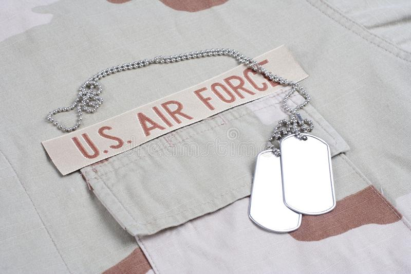 US AIR FORCE branch tape with dog tags on desert camouflage uniform. Background royalty free stock images