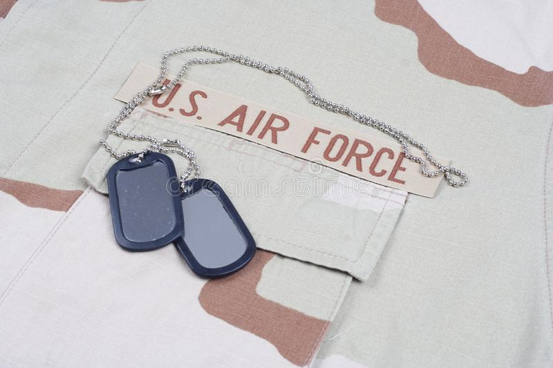 US AIR FORCE branch tape with dog tags on desert camouflage uniform. Background stock images