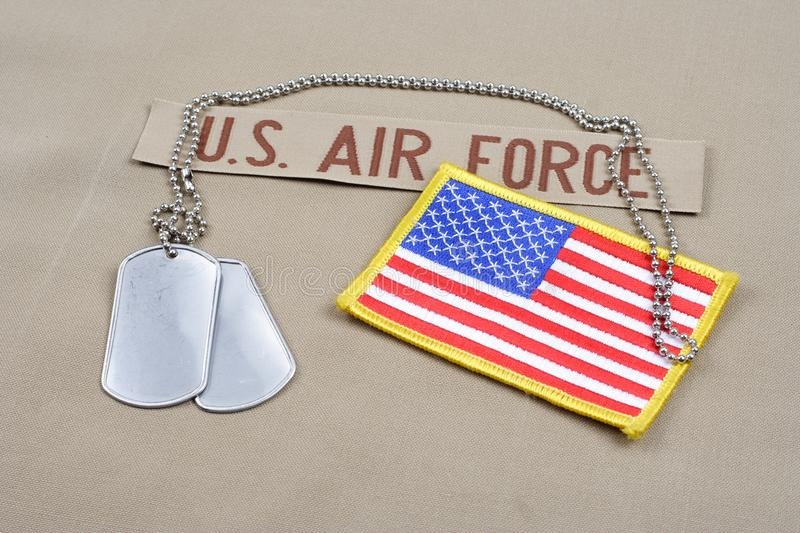 US AIR FORCE branch tape with dog tags and US flag patch on desert camouflage uniform. Background stock photo