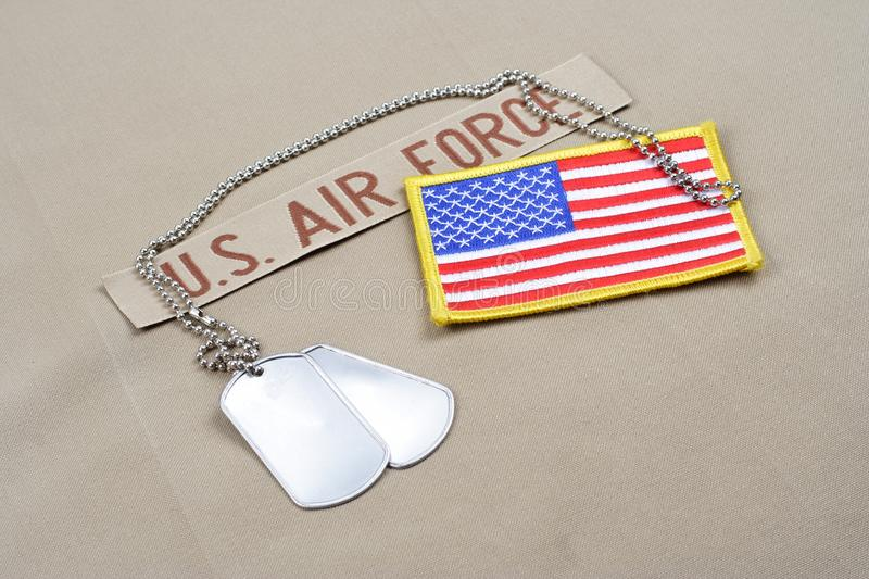 US AIR FORCE branch tape with dog tags and US flag patch on desert camouflage uniform. Background stock image