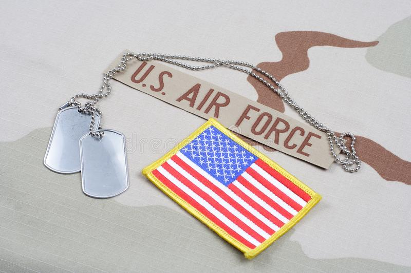 US AIR FORCE branch tape with dog tags and US flag patch on desert camouflage uniform. Background royalty free stock photo
