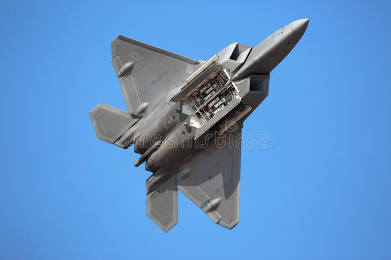 A US Air Force F-22 Raptor performs a demo at airshow with open internal weapon bay. Hillsboro, Oregon  USA - 21 September 2014: A US Air Force F-22 Raptor royalty free stock photo
