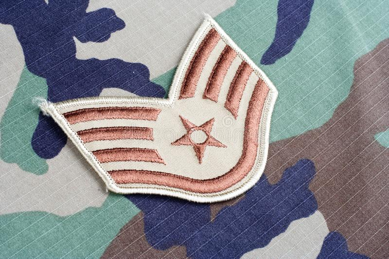US AIR FORCE Staff Sergeant rank patch on woodland camouflage uniform. Background royalty free stock photo
