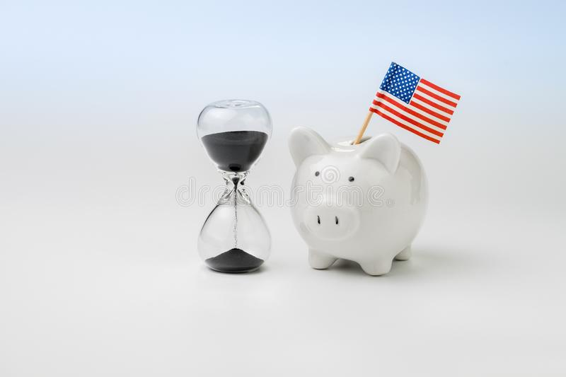 US, America time countdown economics, budget, saving or financial crisis concept, hourglass or sandglass with white piggy bank wi royalty free stock image
