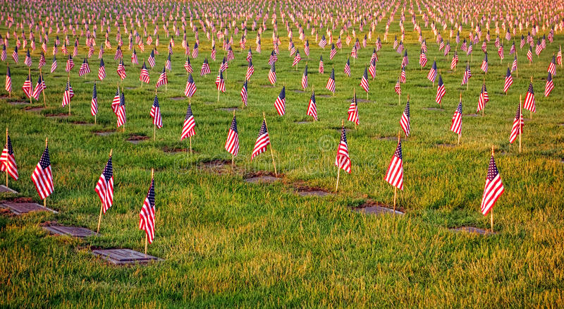 US American Flags on Graves in Veterans Cemetery. Field of patriotic US American flags honoring soldiers graves with respect and dignity in remembrance of royalty free stock photo