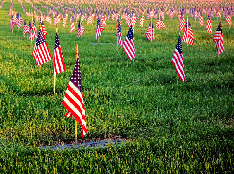 US American Flags Honoring Veterans Cemetery Grave. US American flags planted in honor of veterans graves with dignified respect in patriotic remembrance in a royalty free stock photography
