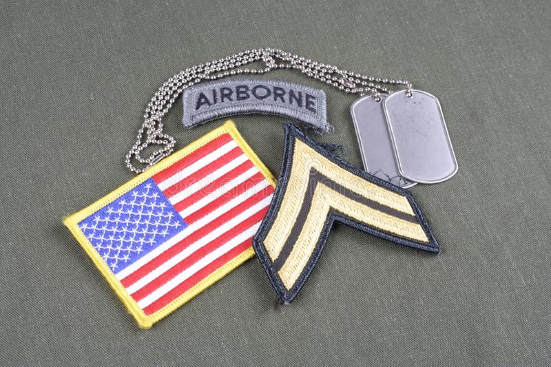 US ARMY Corporal rank patch, airborne tab, flag patch and dog tag on olive green uniform. Background royalty free stock image